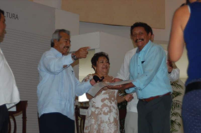 Miguel Ángel Flores Aguilar recibe de manos del delegado de la Secretaria de Educación Pública en Quintana Roo José Manuel Gil Padilla
