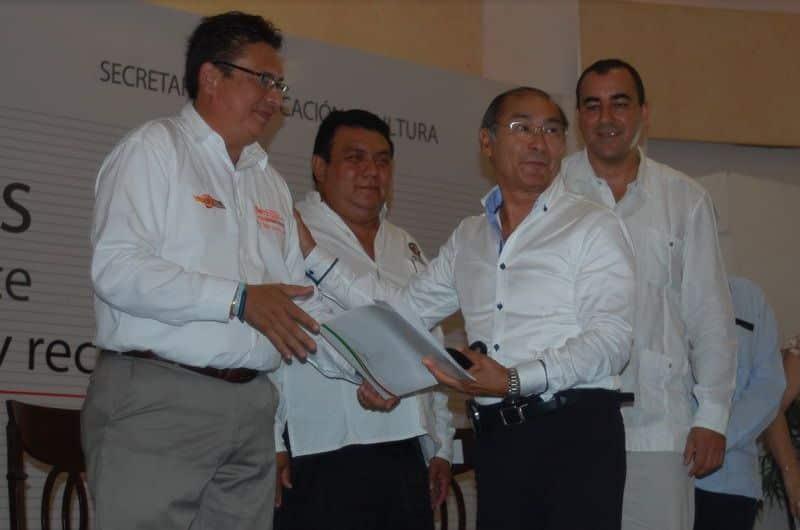 Manuel Hay Lee recibe su reconocimiento por 40 años de servicio de manos de Rafael Gonzales Sabido.