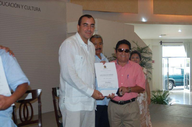 Adán Tadeo Esteban recibe de manos del Secretario de Educación en el Estado Luis Alberto Alonso Ovando.